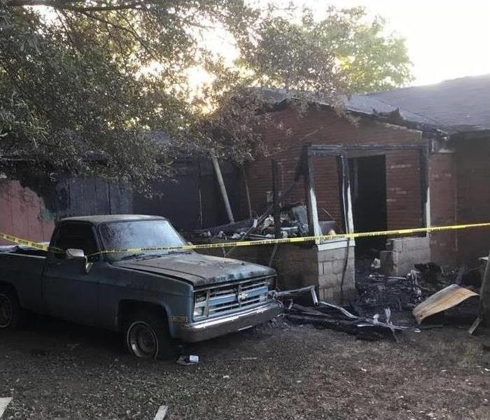 The outside of a burnt house and a car that have windows broken