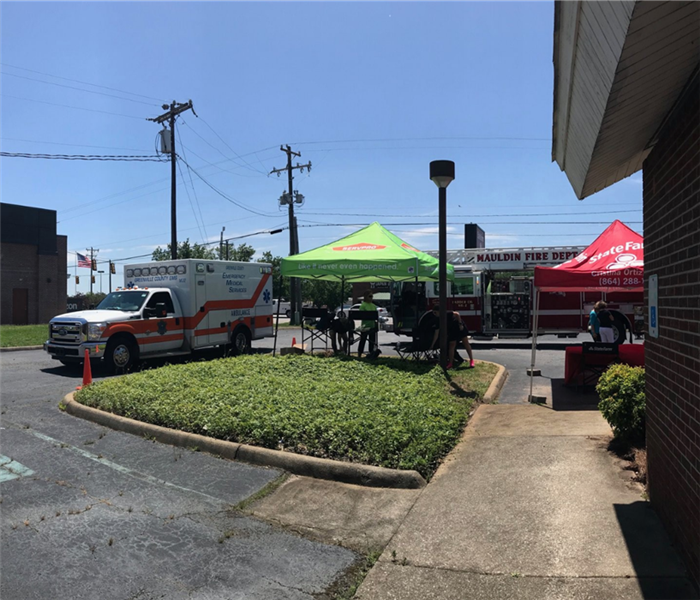 An ambulance, fire truck, and SERVPRO tent in a parking lot