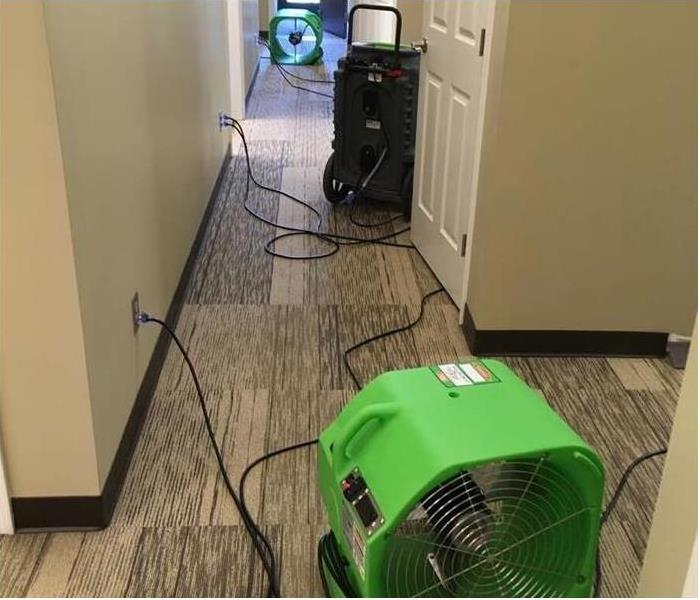A hallway that has 2 fans and a machine drying the carpet floor
