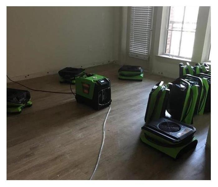Fans and water restoration machines sitting on hardwood floors